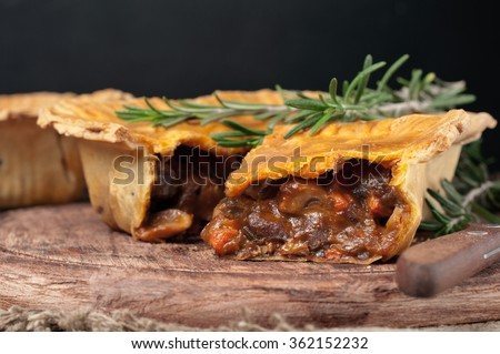 Fresh australian meat pie on the wooden table closeup with copy space, rustic style
