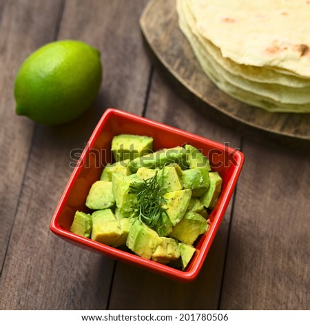 Fresh avocado salad prepared with lime juice, pepper, salt and garnished with fresh coriander leaves, homemade tortillas in the back (Selective Focus, Focus in the middle of the salad)