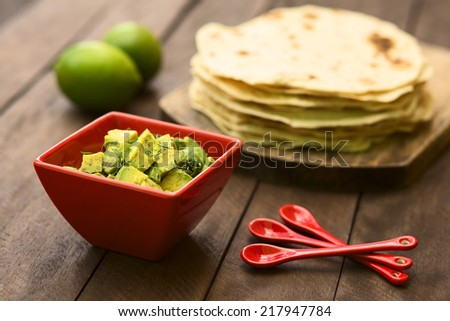 Fresh avocado salad prepared with lime juice, pepper, salt and sprinkled with fresh coriander leaves, homemade tortillas in the back (Selective Focus, Focus in the middle of the salad)