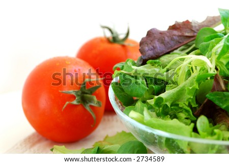 Fresh baby greens salad and tomatoes on white background