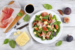 fresh baby spinach, figs, thinly sliced italian ham and tender mozzarella cheese salad on white plate on wooden kitchen worktop with ingredients on background, view from above