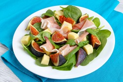 fresh baby spinach, figs, thinly sliced italian ham and tender mozzarella cheese salad on white plate  on  table mat on wooden kitchen table, view from above, close-up