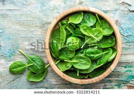 Fresh baby spinach leaves in bowl on wooden background Сток-фото ©