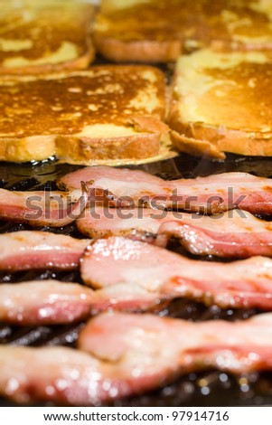 Fresh bacon sizzling on the grill with delicious homemade French Toast for breakfast. - stock photo