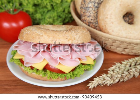 Fresh bagel with ham, tomatoes, cheese and lettuce