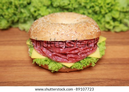 Fresh bagel with salami, cheese and lettuce on a wooden table