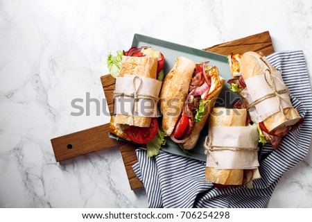 Fresh baguette sandwich bahn-mi styled. Bacon, roasted cheese, tomatoes and lettuce on metallic tray on white marble background. Stok fotoğraf ©