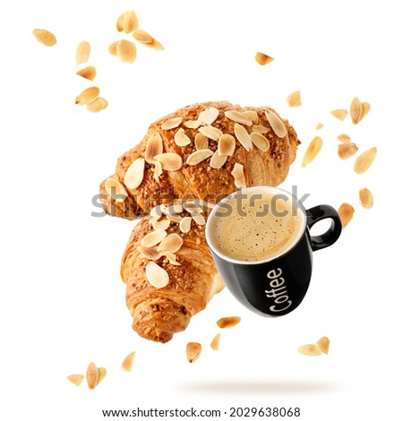 Fresh baked almond  breakfast croissants  with nuts flakes crumbs and black cup hot espresso coffee flying isolated on white background. Two croissants and cup falling. Pastry shop or cafe card.