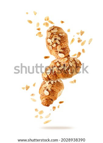 Fresh baked almond  breakfast croissants  with nuts flakes crumbs flying isolated on white background. Three croissants falling. Pastry shop card.