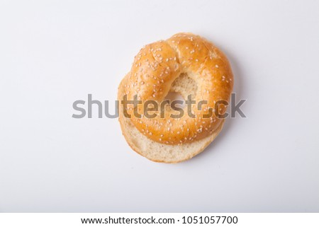 Fresh baked bagle bun with sesame seeds on white background pre-cut for making sandwiches