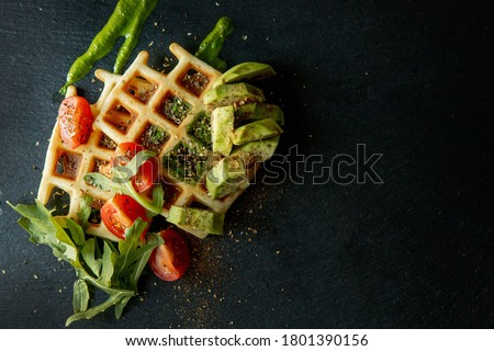 Fresh baked Belgian waffles with arugula, tomatoes and avocado on black a plate. Savory waffles. Breakfast concept. Healthy breakfast. Сток-фото ©