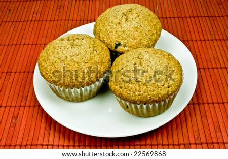 Fresh baked blueberry bran muffins in muffin tin on rusty red placemat