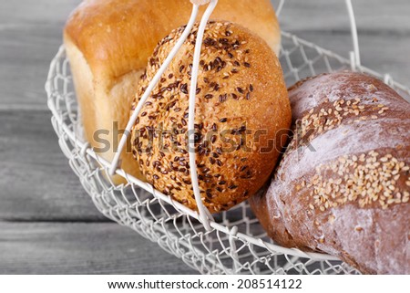Fresh baked bread in basket, on wooden background