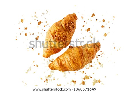 Fresh baked butter and almond nut breakfast croissants  with crumbs flying isolated on white background