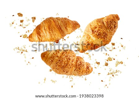 Fresh baked butter and  nut breakfast croissants  with crumbs flying isolated on white background