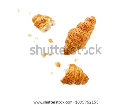 Fresh baked  butter crushed nuts breakfast croissants  and crumbs flying isolated on white background