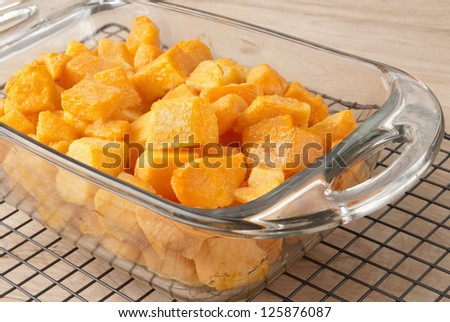 Fresh baked butternut squash drenched in olive oil prior to baking this vegetable casserole. Served in a see through transparent glass pan and is cooling off on a black kitchen cooling rack.