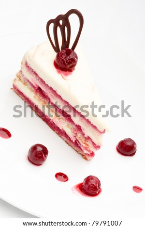 Fresh baked delicious white sponge-cake with cherry on top