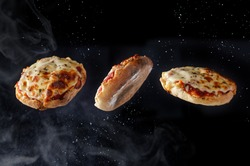 Fresh baked homemade English muffin pizzas flying through the night sky like UFO's