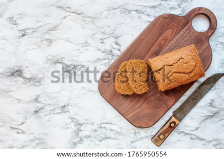 Photo of Fresh baked homemade pumpkin bread with knife over black and white marble background. Image shot from top view.
