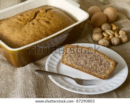 Fresh baked nut cake with ingredients and slice on plate