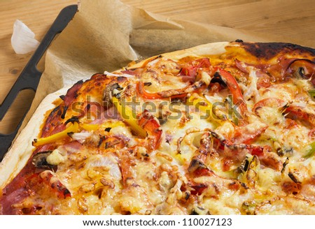 Fresh baked pizza with ham, peppers and cheese on a baking sheet, close-up as detail for Italian food