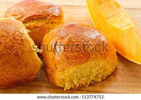 Fresh baked pumpkin buns on a wooden board