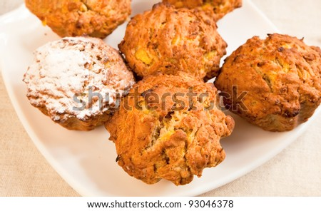 Fresh baked pumpkin muffins on a plate with sugar icing over one of them.