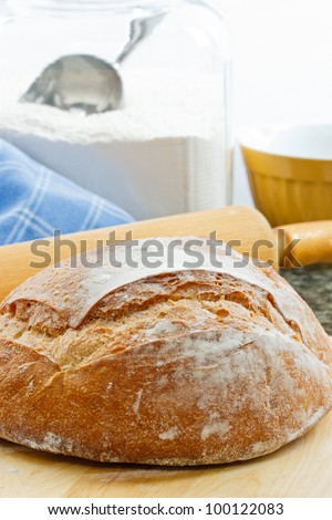 Fresh baked round artisan bread with rolling pin and flour jar in the background