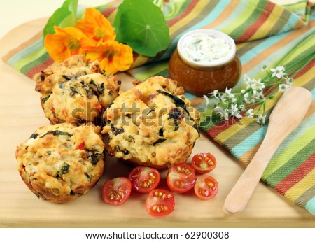 Fresh baked savory muffins with herb spread and cherry tomatoes.