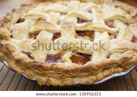 Fresh baked strawberry rhubarb pie cooling on a porch rail