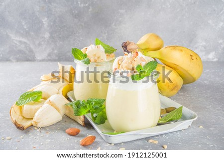 Fresh banana pudding for breakfast, banana yogurt. Sweet dessert in glasses with banana slices and nuts, raw vegetarian snack, on grey concrete background with fresh yellow bananas Foto stock ©