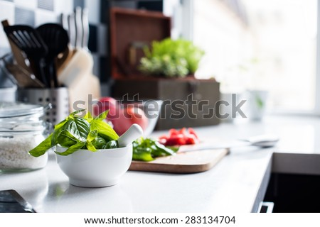Fresh basil in a mortar, chopped tomatoes and ingredients for cooking on the kitchen table, the summer homemade Mediterranean cuisine.
