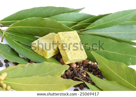 Fresh bay leaves, bouillon cube, whole black pepper and white coriander isolated on white