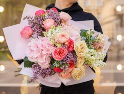 Fresh beautiful flower. Woman holding a big delicate flower bouquet of roses, lilac, astilba, hydrangea and others wrapped in pink paper.