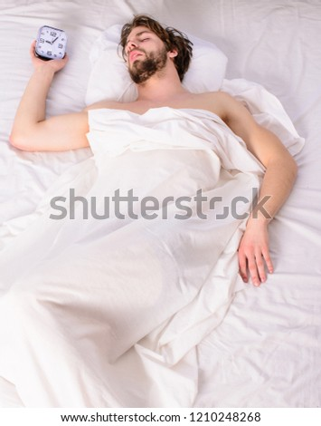Fresh bedclothes concept. Man sleepy drowsy unshaven bearded face covered with blanket having rest. Turn off alarm clock. Man unshaven relaxing bed hold alarm clock. Guy lay under white bedclothes. #1210248268