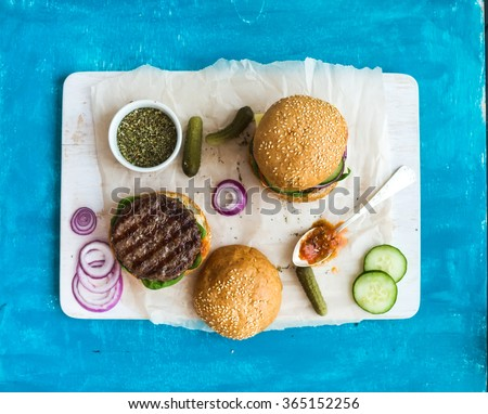 Fresh beef burger with cheese, vegetables and spicy tomato sauce on paper and white serving board, blue wooden background, top view