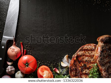Fresh beef steak on a black stone plate. Around are fresh tomatoes in drops of water, sweet and spicy peppers, greens, spices, salt and black pepper. Ideal for the restaurant menu or for intro video #1336322036