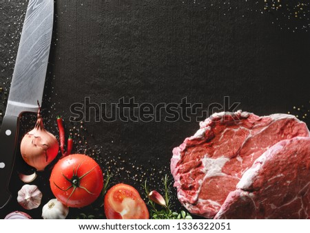 Fresh beef steak on a black stone plate. Around are fresh tomatoes in drops of water, sweet and spicy peppers, greens, spices, salt and black pepper. Ideal for the restaurant menu or for intro video #1336322051