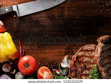 Fresh beef steak on a grunge wood plate. Around are fresh tomatoes in drops of water, sweet and spicy peppers, greens, spices, salt and black pepper. Ideal for the restaurant menu or for intro video #1336322039