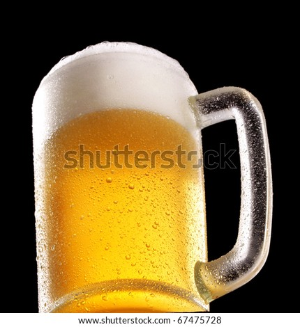 Fresh beer glass on black background.