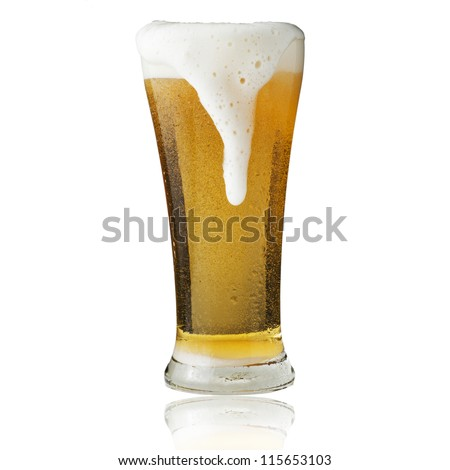 Fresh beer in glass with foam spills on white background