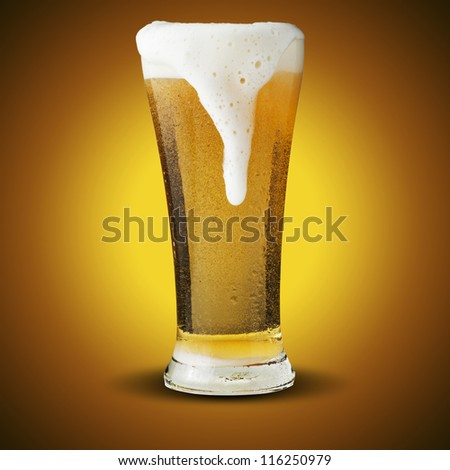 Fresh beer in glass with foam spills on yellow background