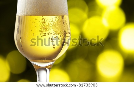 fresh beer on a cup on a lights background