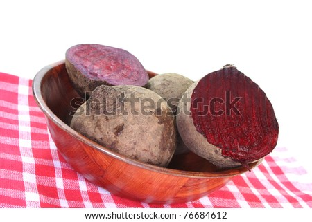fresh beet root in a wooden bowl on a white background