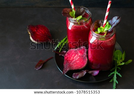 Fresh beetroot smoothie, beet, arugula and lettuce leaves on dark wooden background