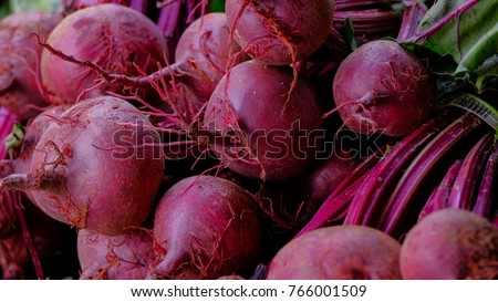 Fresh beets and beet tops  lie on farmer market counter.farmer's market