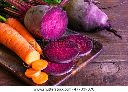 fresh beets and carrots with sliced vegetables on wooden background. food