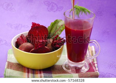 fresh beets with leaves and clear soup in tall glass