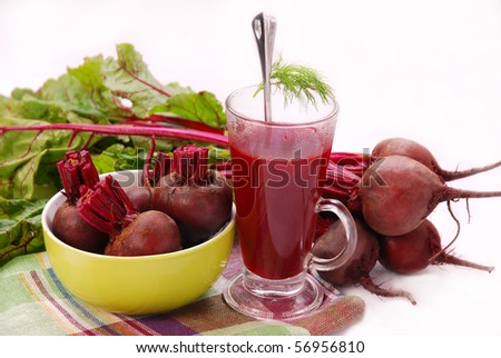fresh beets with leaves and clear soup in tall glass isolated on white